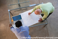 Stock photo of Architects working with blueprints on table with laptop taken from overhead.